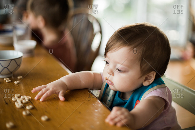 Small baby reaching for cereal while sitting at the table