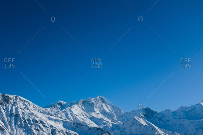 Snow covered mountain peaks and blue sky