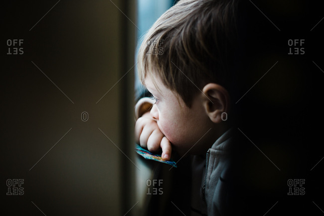 Little boy watches out the window of a train