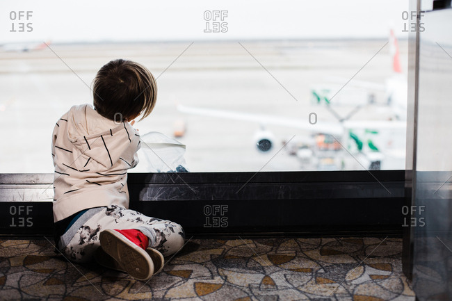 Little boy looking at airplanes while he waits for a flight