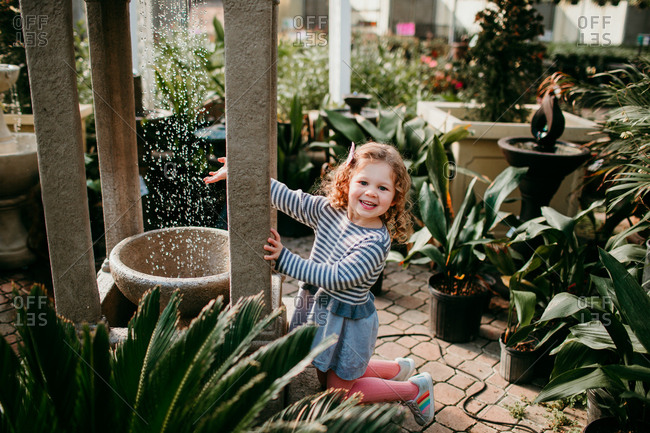 Little girl playing with water fountain in a garden center