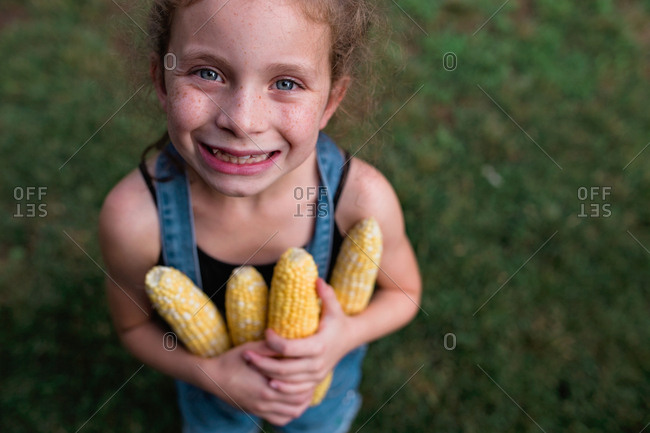 Girl smiling holding fresh picked corn