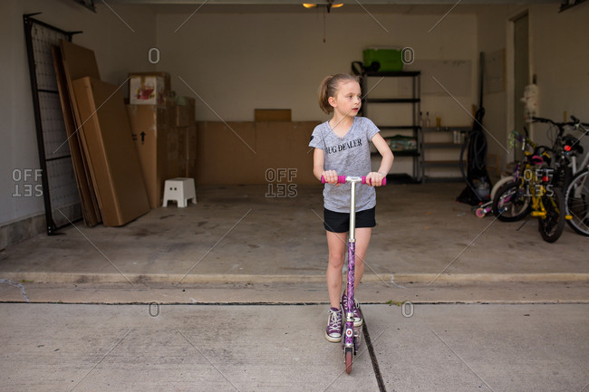 Girl riding scooter in front of moving boxes in a garage