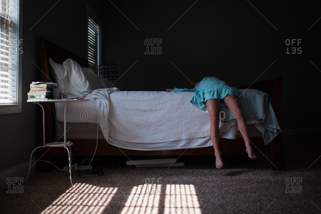 Girl lying with her feet off the bed