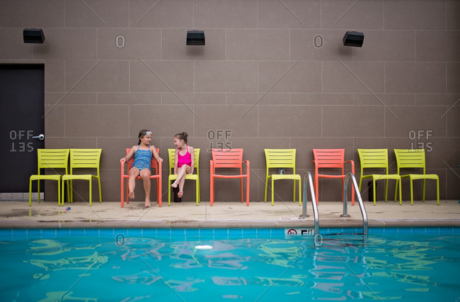 Girls talking on chairs by pool