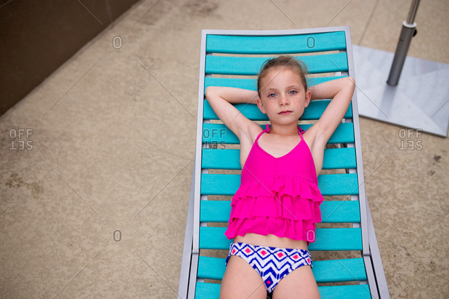 Sad girl laying out by the pool