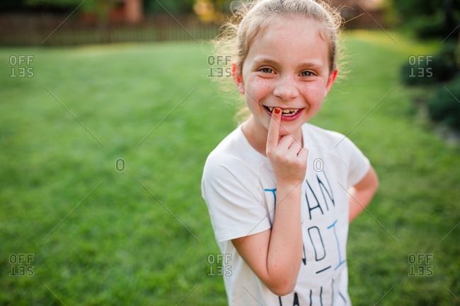 Girl looking at camera with finger to her tooth