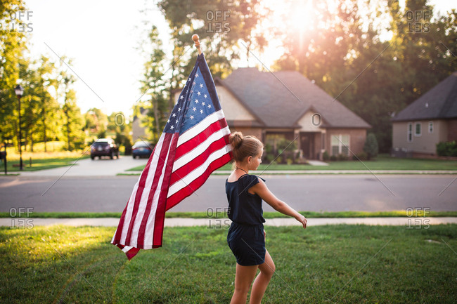 Girl in front of house with big American flag