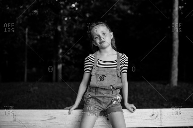 Girl in overalls making a silly face