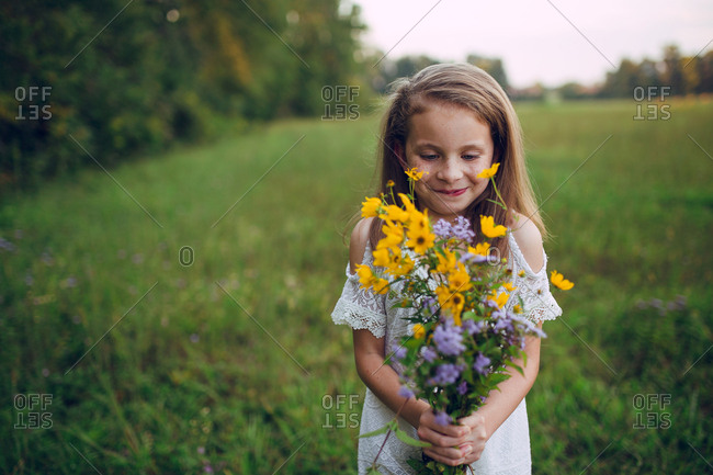 Girl holding flowers and looking at them happy