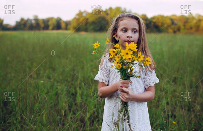 Girl holding a bunch of yellow flowers looking away