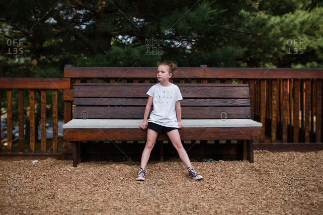 Girl slightly sitting on bench