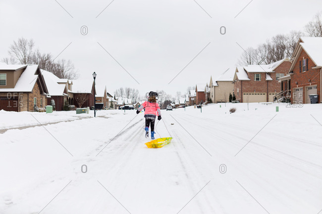 Girl running down street with sled behind her