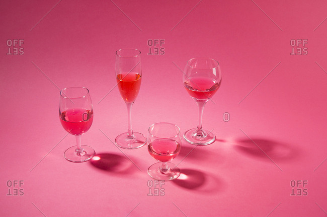 Wine in glasses on pink background