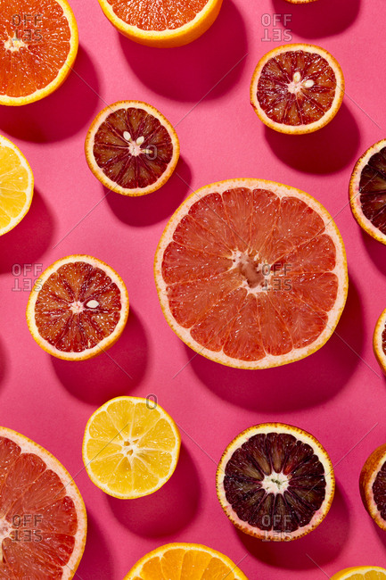 Variety of citrus fruit slices on a pink background