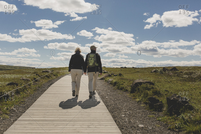 Southwest Iceland - July 9, 2017: A man and woman walking up a path holding hands in the Southwest region of Iceland on an idyllic sunny day