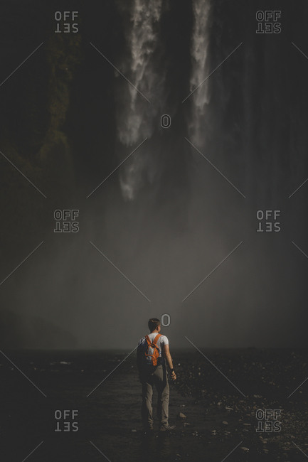 Traveler stopping at the foot of Skogafoss waterfalls in Iceland to take a photo