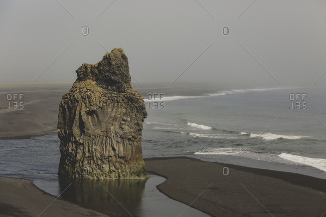 Rock formations on the black beach along the Dyrholaey peninsula of south Iceland