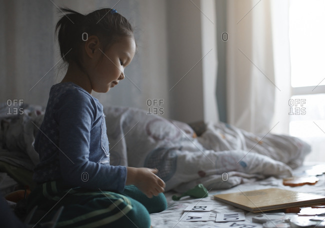 Side view of girl playing while sitting on bed at home