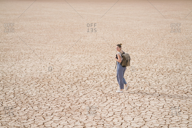 Side view of woman with backpack walking on barren landscape