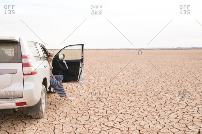 Portrait of woman sitting in off-road vehicle at desert against sky