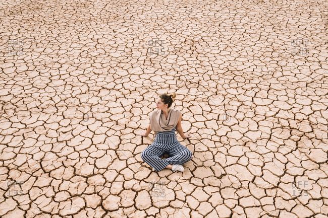 High angle view of woman sitting on barren landscape