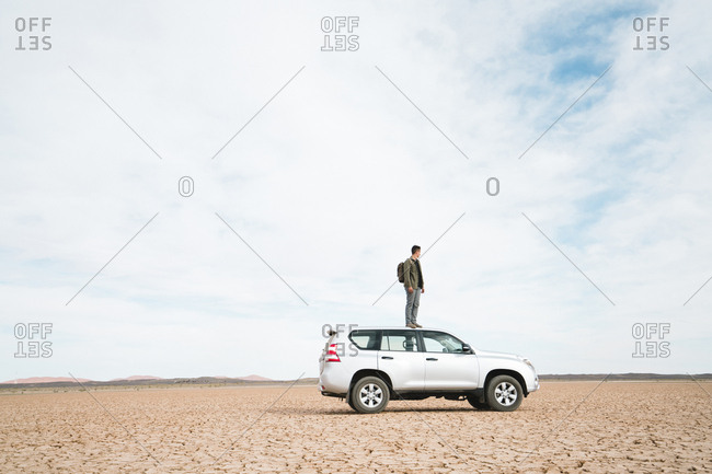 Side view of man standing on off-road vehicle at barren landscape against cloudy sky
