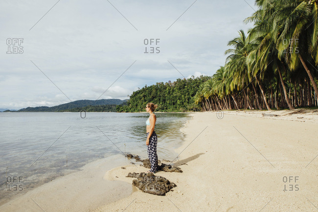 Side view of young woman standing at beach against sky