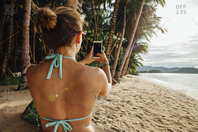 Rear view of young woman using smart phone at beach
