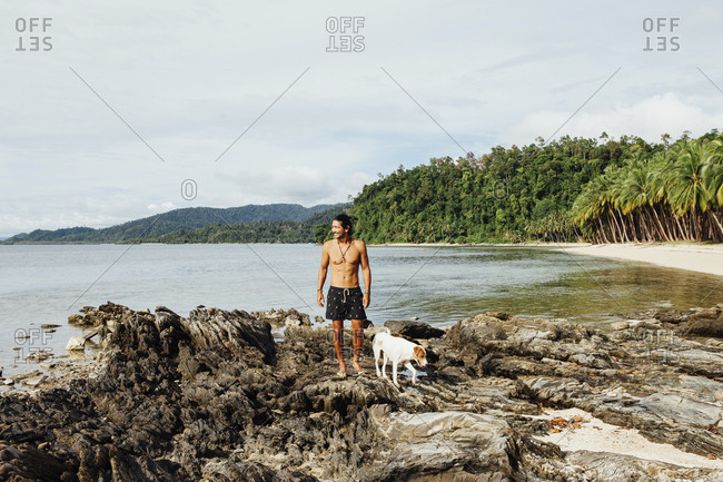 Shirtless hiker with dog standing on rocks against sky at beach