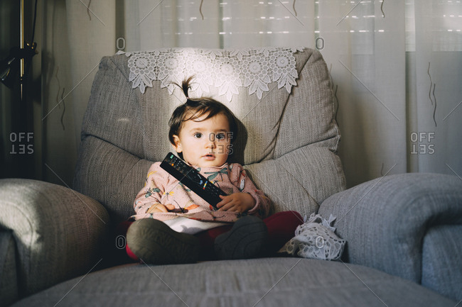 Cute baby girl with remote control sitting on armchair at home