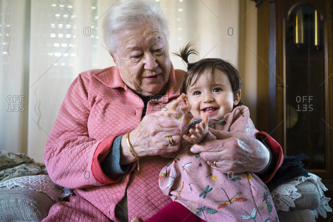 Grandmother playing with cheerful granddaughter at home