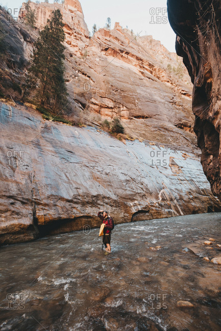 Hiker standing in river amidst rock formations at Zion National Park
