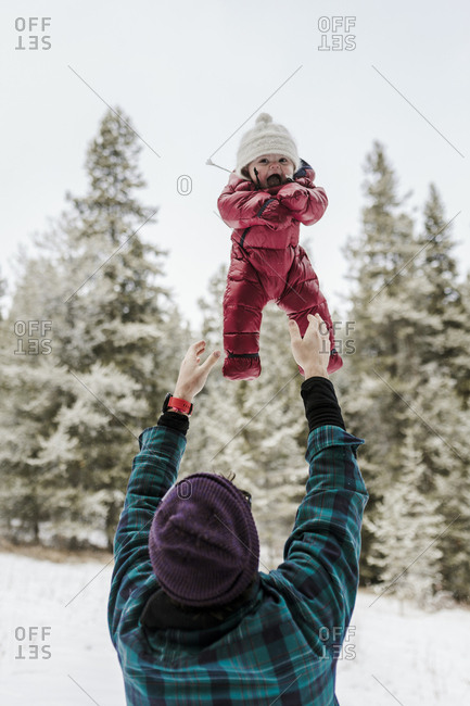 Rear view of father throwing cute daughter while standing in forest during winter