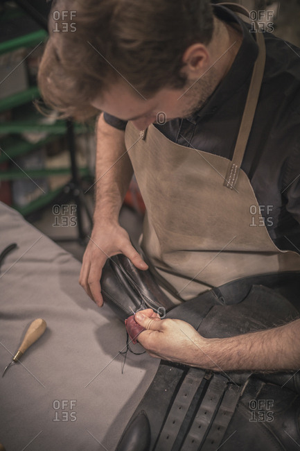 High angle view of shoemaker making shoes at workbench in workshop