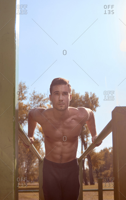 Low angle view of shirtless man exercising on parallel bars against sky at park