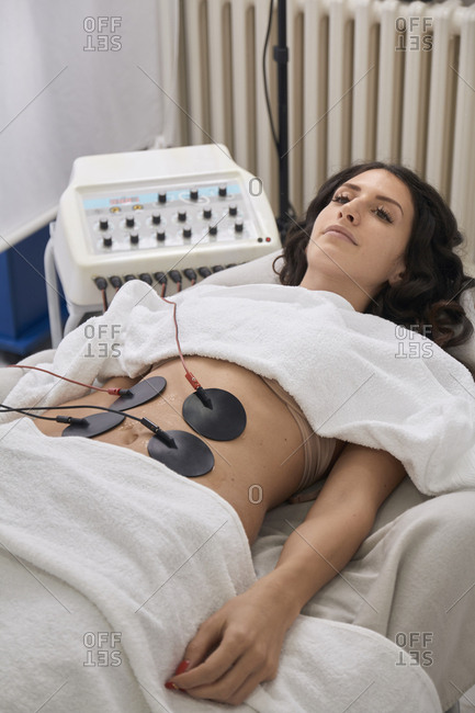 High angle view of patient having electrodes physical therapy while lying at medical clinic