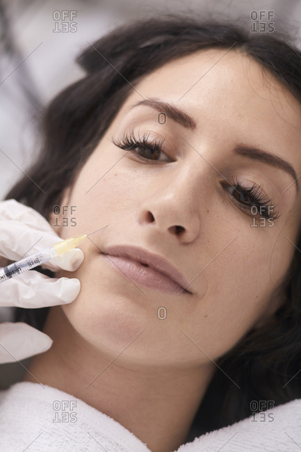 Cropped hands of female doctor injecting liquid injection on patient\'s face at medical clinic