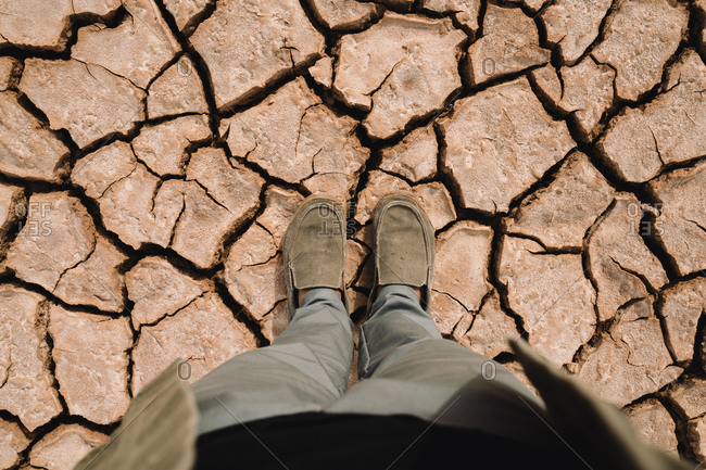 Low section of man standing at barren landscape