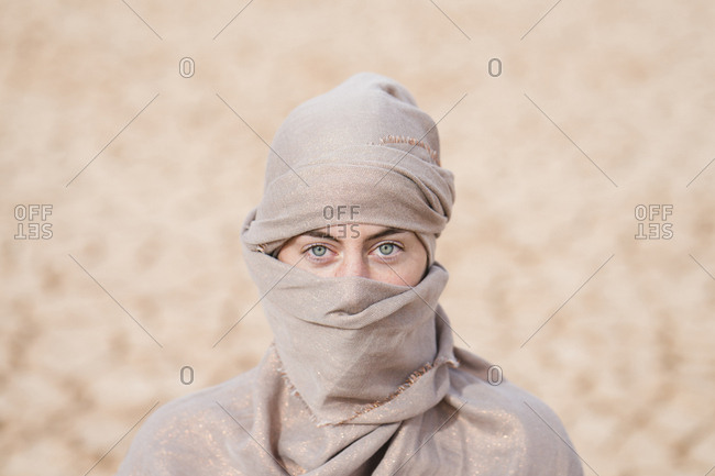 Portrait of woman wearing scarf standing at barren landscape
