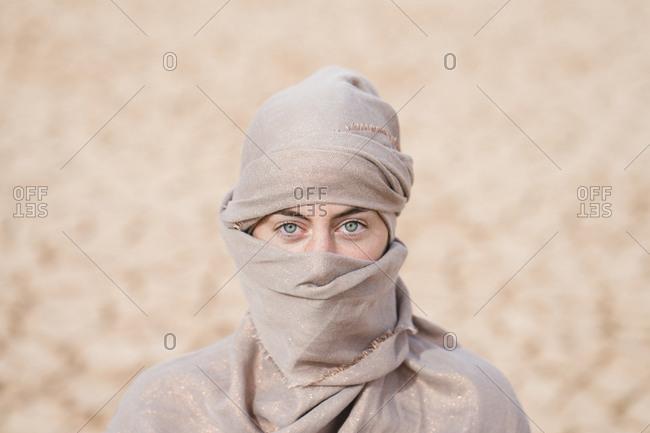 Portrait of woman wearing scarf standing at barren landscape