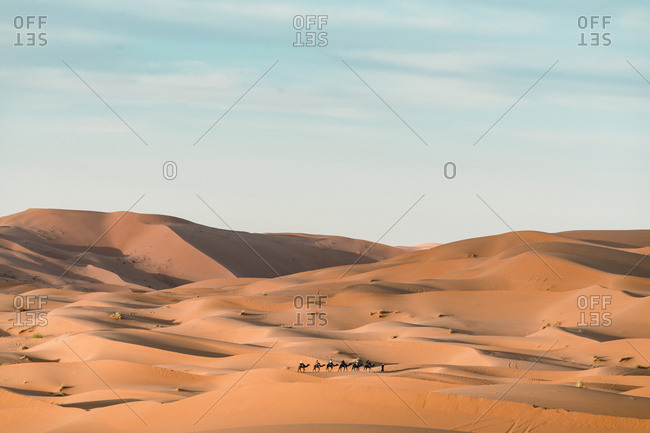 People with camels at Merzouga desert against sky