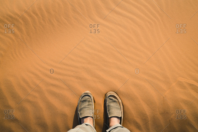 Low section of man standing on sand at Merzouga desert