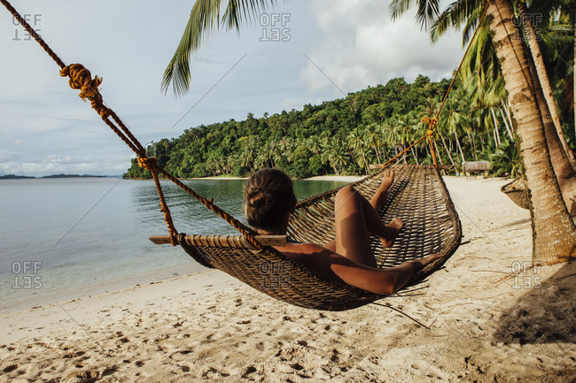 Young woman resting in hammock at beach