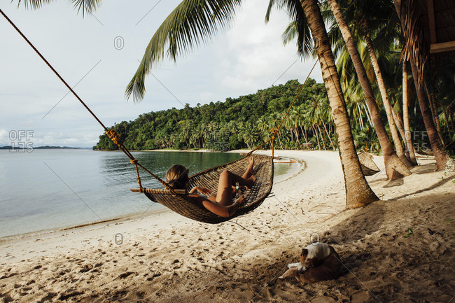 Young woman resting in hammock by dog at beach