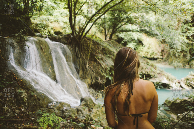 Young woman wearing bikini top while looking at view in forest