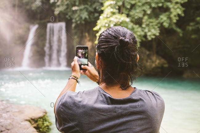 Rear view of man photographing waterfall with smart phone