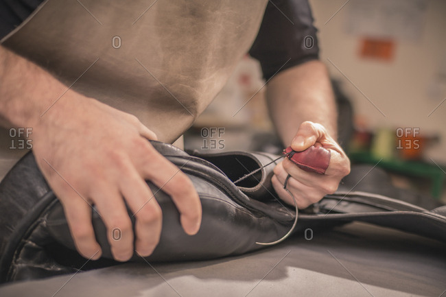 Midsection of shoemaker making shoes at workshop