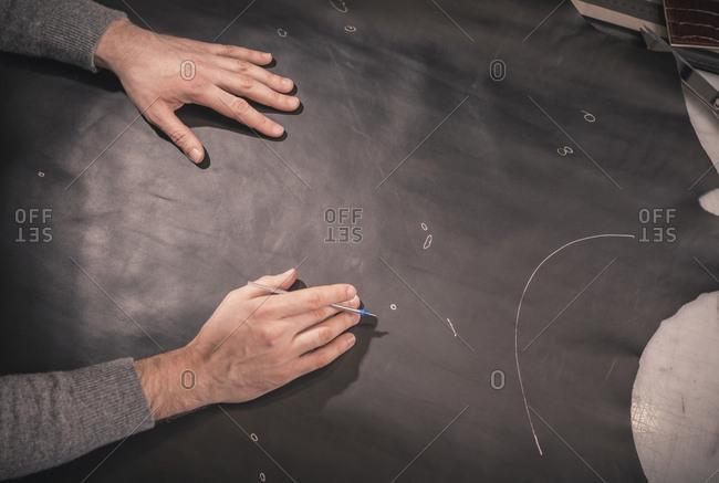 cropped hands of shoemaker measuring leather on workbench at workshop