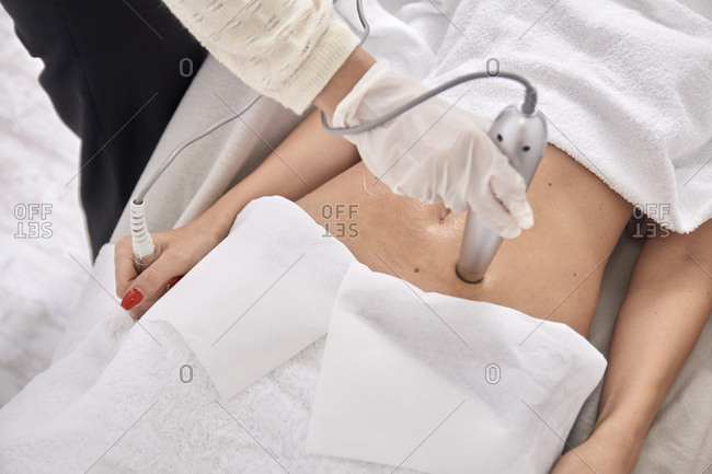 High angle view of female doctor using medical equipment while treating patient at medical clinic